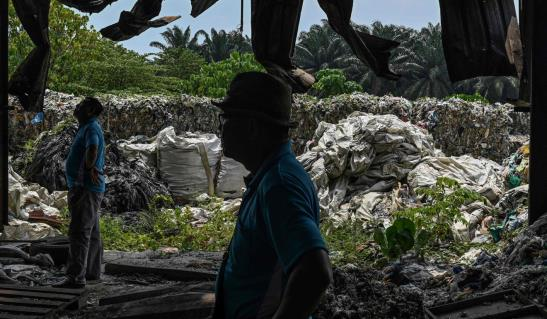 epresentatives of an environmentalist NGO inspect an abandoned plastic waste facto